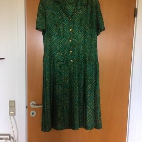 Fantastisk smuk 70'er vintage - retro kjole str L med dropwaist og i skinnende polyester. Kjolen er i perfekt stand. Kjolen har guldknapper og plisseret underdel. Mål: længde: 108 cm, bryst: 2*47 cm, talje: 2*43 cm.