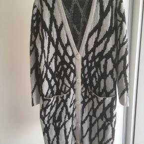 Mærke: Gestuz Style: ALEA CARDIGAN Model design: 900850 Størrelse: xs, men passer også S og M. Stor i størrelsen Farve: sort og råhvid og metal snor Materiale: 40% viscose, 29% Acryl, 20% uld, 10% nylon, 10% metallic Trøjen: en lang trøje, med knapper foran Stand: brugt få gange  Sælges: kr  250