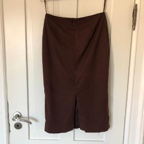 Enkel højtaljet nederdel i flot brun farve. Skjult lynlås og slids bagpå.   Foret er gået lidt i stykker, men betyder ikke noget for brugen.   Mulighed for afhentning i Aarhus C  Se også mine andre annoncer 😊
