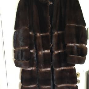 Supersmuk og anvendelig mink frakke med slangeskind. Minken er i rigtig fin stand.