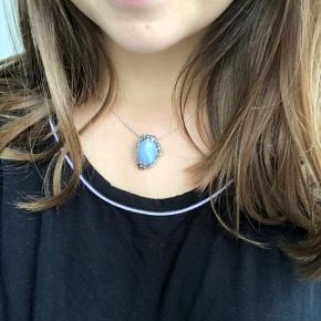"""Smuk halskæde i ægte sølv og med en stor flot sten i forskellige nuancer af blå og en fin blomsterkant i sølv. Aldrig brugt. Købt i guldsmed forretning i Kalundborg """"Morten Nygaard"""" - æske herfra følger med."""