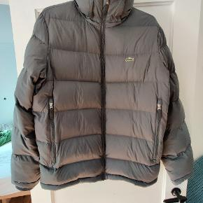 Lacoste jakke med 80% down dun.  Jakken er vanvittig let og vanvittig varm i de kolde måneder :)   Ingen tegn på slid   - har medfølgende hætte :)