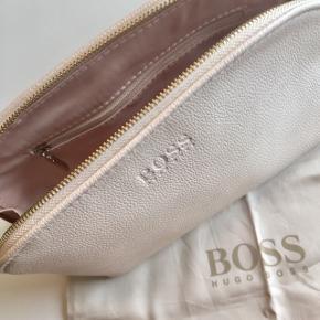 Hugo Boss toilettaske/make-up pung med guld lynlås i farven cremefarvet. Indeni er der en lille lynlås. Der medfølger en pose dertil med Hugo Boss logo 🦢  Byd gerne kan både afhentes i Århus C og sendes på købers regning 📮✉️