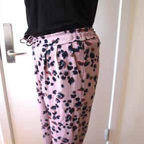 Casual bukser med print i en mørk rosa.  Regular fit,  let materiale, high waist med snører og stiklommer + snydelomme bagpå.  96% polyester og 4% elastan  mål:  talje: 40cm hofte: 50cm lår: 30cm indvendig benlængde: 69cm