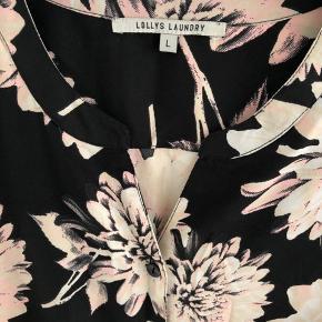 Tunika/ stor skjorte med lange ærmer og knapper hele vejen ned foran. Lange ærmer. Sort bund med hvide og sart Rosa blomster. 100% polyester. God stand og almindelig i størrelsen.
