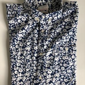 Fin mørkeblå skjorte med hvidt blomsterprint. Brystlomme og lange ærmer.  Str.: L Materiale: 100 % økologisk bomuld.  Brugt få gange.  Nypris ca. 649 kr.