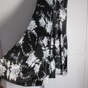Smuk lang nederdel i sort med hvide og grå blomster. Lynlås i siden og bæltestropper. Fra Jindi Fashion i str. M. Liv: 43 x 2 Længde: 108 Brugt en enkelt gang. Små tråde der er gået forskellige steder. Deraf prisen.  Pris: 150,- + evt. porto  Kan ses og prøves hos mig i København NV. Kig også forbi mine mange andre annoncer med tøj, sko og tasker. Rabat ved køb af mere.  #GøhlerSellout