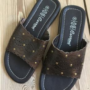 Sød og smart sandal, mørkebrun med hulmønster og enkelte nitter. Aldrig brugt. Sendes gerne. Køber betaler porto.