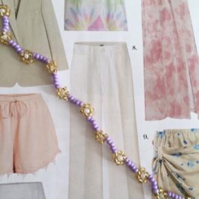 Smukt håndlavet perle armbånd med blomster i lilla, guld og hvid. Brugt få gange, næsten som ny.   Ved handel over mobilepay 85 inkl.   Se også mine andre fine håndlavede perlesmykker 🌼