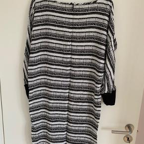 Sort/hvid Mønstret kjole fra Saint-Tropez. Fungerer både med bare ben eller strømpebukser under. 3/4 lange ærmer, som afsluttes med en bred stretchy kant.  Den er str. Small, men kan også passes af en medium.