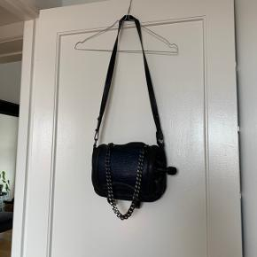 Lækker sort crossbody taske i ægte læder.  Har fine mørkeblå detaljer. To store lynlås lommer og en lille lynlås lomme inden i. Aftagelig hank, så kan laves om til en clutch.   #Secondchancesummer  Se også min profil og alle mine mange andre flotte og billige varer jeg har til salg 🌸  Tryk køb nu eller bed mig oprette en handel, hvis du er interesseret ☺️  Tags: Sort - blå - mørkeblå - læder - taske - skuldertaske - slangeskind - cross body - crossbody - cross-body - crossbody-taske - clutch - kæde