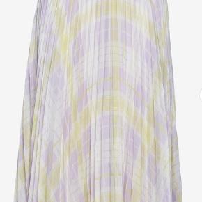 Plisseret nederdel af florlet stof med tern i sart gul, lilla og hvid. Lynlås i siden. Længde til under knæene. Brug den med en lækker strik som kontrast til det feminine - eller med en enkel bluse og stiletter. Prisen er pp & ts