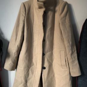 Fin frakke fra Mango. Lidt krøllet fra at have været pakket ud over sommeren men det retter sig ud.  Består af 40% uld.   Køber betaler fragt.