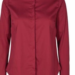 Smuk og klassisk skjorte fra Mos Mosh. Skjorten har rund hals og skjult knaplukning på front. Skjorten er med lange ærmer med flæsekant og knaplukning. Modellen er slimfit og str xs