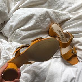 Info: orange heeled sandals fra Zara, prøvet på indenfor. Står bare og samler støv, er i ruskind og med fine miu miu inspirerede spænder foran Pris: 300 Nypris: 449 Mærke: zara Stand: som nye Størrelse: 39 Andet: i orange ruskind med sjove spændedetaljer Fragt: Jeg foretrækker at sende med tracking (evt. Dao for kun 33 kr.) men kan også møde ved Nørreport.  OBS: Varen kommer fra et røgfrit hjem. Hvis du gerne vil se den først, skal du være velkommen til at mødes i indre by/Nørreport, København. Jeg tager ikke flere billeder end dem på annoncen, og jeg forbeholder mig retten til ikke at besvare kommentarer ang. overstående allerede besvarede spørgsmål. (Eksempelvis kan det ske, at jeg ikke svarer hvis der bliver spurgt om bytte og at jeg allerede har skrevet tydeligt, at jeg altså ikke bytter. Det tager tid at besvare, men kun et sekund at læse sig frem til. Derimod må du/i selvfølgelig altid spørge!)   Tjek også gerne mine andre annoncer, bestående af mærker som Ganni, Chanel, Acne, Gina tricot, Asos, Baum & Pferdgarten, COS, Arket, & Other stories, miu miu, en masse vintage mm.