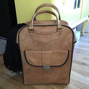 Virkelig lækker retro taske i lækker brun farve.   Måler ca  47 cm høj 36 cm lang 18 cm bred  Det er ikke læder, den er dejlig fast og let i det. Kan bruges som taske eller fx som dekorativ opbevaring til fx tæppe eller legetøj.   Kan sendes på købers regning med dao eller afhentes i Tilst.