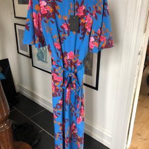 Den smukkeste buksedragt i skønne farver. Der er en flot åbning i ryggen og med bindebånd.
