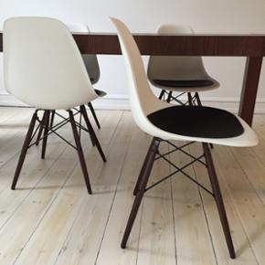 4 x Eames stol (DSW) hvid med mørkbejset ben 4 x puder i sort læder  Design: Charles & Ray Eames for Vitra, 2003.  Materiale:  Hvid plastic skal. Ben i mørkbejdset ahorn.  Nypris nu: 14.223 kr (3.556 kr pr stk)