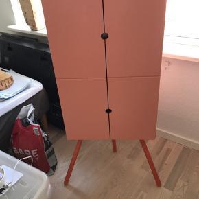 Fint lille hjørneskab fra IKEA. Et lille bitte mærke men ellers i rigtig god stand. Koral/orangefarvet. 110 cm høj (inkl. ben), skabet 80 cm høj, 50 cm bred.