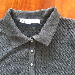 Fin, let strikket top med korte ærmer og lille krave. Flettet struktur. Små knappe ved halsen. Aldrig brugt.