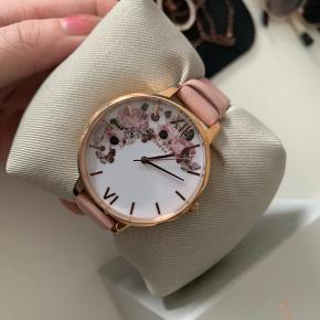 Super fint og feminint ur fra Olivia Burton. Stortset ubrugt (prøvet på én gang) Nyprisen var 900kr.  Salgspris 300kr