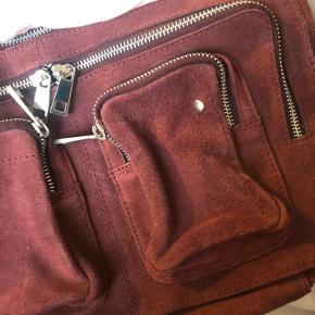 Flot rød/bordeaux ruskinds Nunoo taske, med remme så den både kan bruges som skuldertaske og crossbody.  Helt pæn og ren udenpå og indeni - dog med nogle mørke striber bagpå (ses på billede 3).