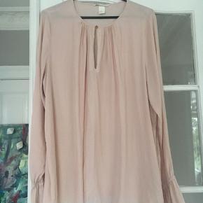 Super fin boheme bluse med lukning med lille knap og elastik og flæser ved ærmerne. Flot støvet rosa i farven.