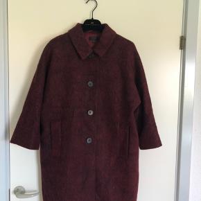 Fin uldfrakke fra COS med 3/4 ærmer i kimono-snit. Brugt kun 3 gange, sælges da jeg sparer op til noget andet.  Farven gengives bedst på billede 2&3   Fra røg- og dyrefrit hjem. Sendes med DAO eller kan afhentes i Fredericia Jeg giver hverken reklamationsret eller fortrydelsesret ved handel over mobilepay (jeg er en privat sælger). Jeg handler dog gerne gennem Tradonopay og de dermed gældende regler.
