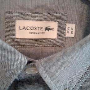 Lækker skjorte fra Lacoste.  Ubrugt med prismærket.  Størrelse 44 ( XL ) Regular fit.   2019 model.  Nypris = 800 kr.  PRISEN ER IKKE TIL FORHANDLING.
