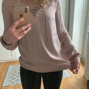 Sød rosa skjorte trøje fra Saint Tropez med binde funktion fortil. Brugt med uden brugsspor. Har elastik forneden som går at man kan give trøjen forskellige udtryk.