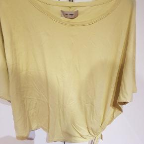 Super fin t shirt med knude detalje i den ene side..ikke skrig gul. En læs model. Farven er lidt svær at gengive