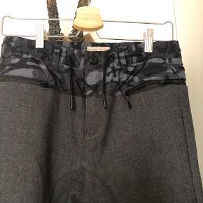 Fede bukser med lynlås i hofterne, elastik i buksekanten. Bindebånd i taljen