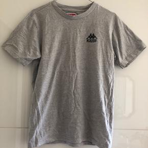 Klassisk Kappa tee med logo på ryggen. Kan også bruges af en Small.