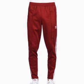 Fedeste mørk rød Adidas buks/chinos ligende  I kraftigere stof  Med elastik i talje og lynlås lommer   Str passer ca 164 i længde vil jeg mene   I perfekt stand Ingen slid , huller el ligende   Vasket en gang  Farve intakt  Nypris 500  Sælges kun ved realistisk bud