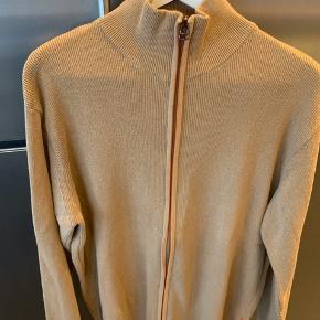 Fin camel farvet strik cardigan med en tyng orange streg ved lynlås   Mål: Bryst: 2 x 75 cm Længde: 70 cm