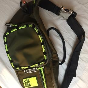 Ganni Tech fabric bæltetaske  Justerbar bælte med stort spænde.  Mål: L:50 cm. H:22 cm. B:8 cm.