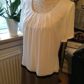 Kjolen er i farverne hvid og beige - og et smalt sort bånd. Kjolen har stadig prismærke på. Ny pris kr 999,-.