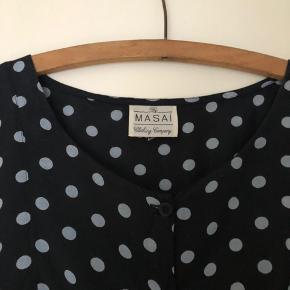 Masai kjole eller lang skjorte i sort med blå/grå prikker. Går lidt ind under brystet og god vidde ned over hofterne.  Længde 94 cm.