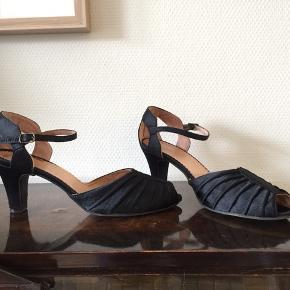 Sort satin med feminine draperinger. Sandaler/festsko med 6 cm hæl.  Blødt skind indvendigt.  Str 39. Hæl 6 cm.