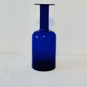 Klassisk vase af Otto Brauer for Holmegaard i 1959. Karakteristisk med lang hals og stor krop. Udført i koboltblå transparent glas. Højde: 25,5 cm Diameter: 9,5 cm