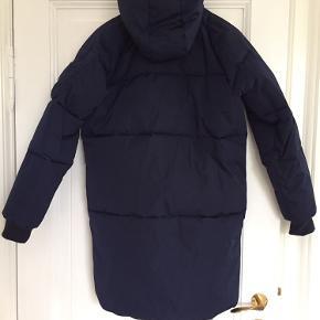 Super lækker padded vinter jakke med hætte. Blå med bordeux foer. 1/2 Brystvidde - 58 cm Skulder og ærmelængde - 77 cm Længde fra mb. - 90 cm