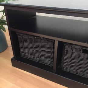 Sort møbel, som kan bruge som bænk (med tilhørende hynde), som tv-møbel eller andet. Møblet har 3 sorte flettede kurver.  Mål: B95xD35xH45