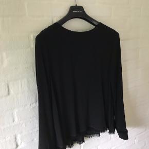 Smuk Fringes bluse, sort 100 % silke i str. L  med fine detaljer fra Kokoon. Blusen har lange ærmer, et enkelt og stilrent snit og frynsedetaljer forneden og på ærmerne. Den har knapper hele vejen langs ryggen  - Brugt få gange - Pæn stand. MP 700,- PP