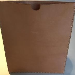 Brand: Kernelæder patina Varetype: Læder iPad/ tablet cover Størrelse: Ipad Farve: Brun  Kernelæder iPadcover.  Enkelt, stilrent, håndlavet og nordisk.  Coveret laves efter mål ved bestilling, og vi kan derfor tilbyde til alle typer iPad eller tablets.  Vi skal derfor vide hvilken type det er til, eller et stramt mål.  Disse laves i ældre kernelæder, derfor har de fra start en skøn patina og spor af forgangen tid.  Læder er et natur materiale, hvor ikke to stykker er ens og alt er håndlavet, derfor kan de variere i udtryk.  Pris 399kr  Kan afhentes i Aalborg, eller sendes med DAO mod Porto på 37kr