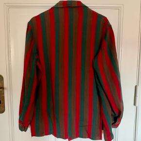 Vintage jakke/blazer i en form for bomuld, tror jeg. Jakken har vertikale striber i rød/grøn/brun og to lommer. Den er ca str 40, men passer bredt afhængig af ønsket fit.
