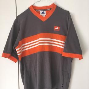 Super fed vintage Adidas T-shirt, den har dog mange år på CV'et hvilket betyder mange gange i vaskemaskinen. Men ellers er den super fin.