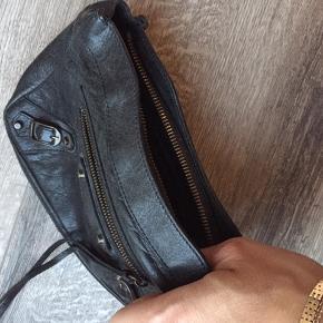 """Lille lækker clutch i meget fin stand  Den er ikke brugt ret meget.  Kan bruges som make up taske, clutch eller en """"samler"""" i en shopper.  Måler 14x20, classique trousse  Dustbag og kvittering medfølger Købt i Balenciaga i London"""