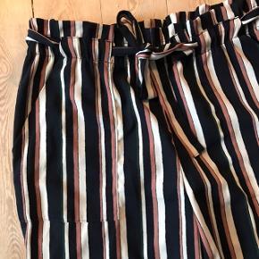 Smukke stribede bukser fra JDY i str. L 🍬 loose fit, skøn model at have på. Bindebånd, så de er fleksible i størrelsen 💕 Har en lille plet foran, se billede.   Bemærk - afhentes ved Harald Jensens plads eller sendes med dao. Bytter ikke 🌙  💫 Bukser stribet stribede loose oversize løse