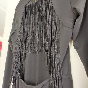 Denne sorte lårkorte kjoler er perfekt til en sjov bytur. Den åbne ryg med sorte flæser er især en både flot og sjov detalje. Den er brugt 1 gang, men var lige kort nok til min smag, hvorfor jeg nu sælger den.