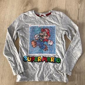 Grå bluse med vendbare palietter med Super Mario, str. 122/128, H&M, brugt men pæn, minimalt med vaskefnuller. 10% af prisen går til Kræftens Bekæmpelse (Team Vejdik, Stafet For Livet) Se mere på mostermette.dk (IG845)